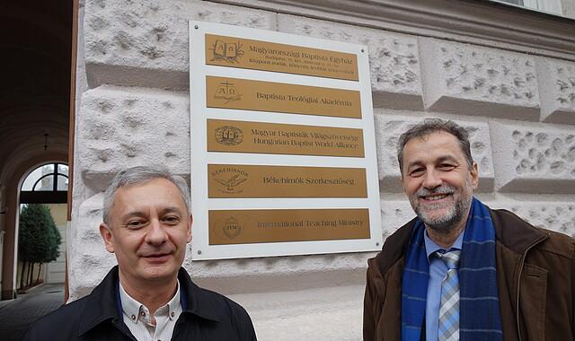 István Durkó und János Papp vor Akademie und Zentrale der Baptisten
